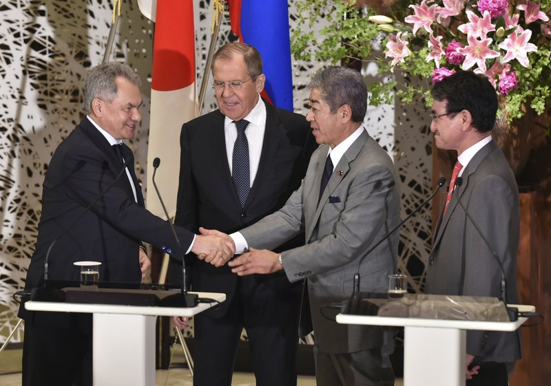 Japan's Defence Minister Takeshi Iwaya, second right, shakes hands with Russia's Defence Minister Sergei Shoigu, left, while Japan's Foreign Minister Taro Kono, right, and Russia's Foreign Minister Sergei Lavrov, second left, look on after their 2+2 joint press conference at the Iikura Guest House in Tokyo, Thursday, May 30, 2019. (Kazuhiro Nogi/Pool Photo via AP)