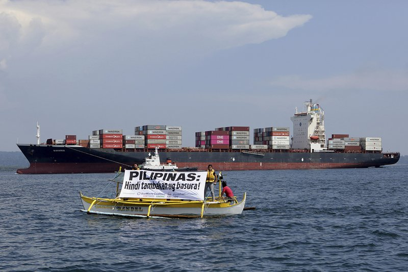 In this image released by Greenpeace, Greenpeace activists and other environmental organizations display a banner as the cargo ship MV Bavaria, the container vessel allegedly hired to ship back the 69 containers loaded with garbage from Canada, slowly enters the mouth of Subic Bay, Thursday, May 30, 2019 in Subic, Zambales province west of Manila, Philippines. The environmental groups are calling on the Philippine government to ban all waste imports into the country and ratify the Basel Ban Amendment. The banner reads: