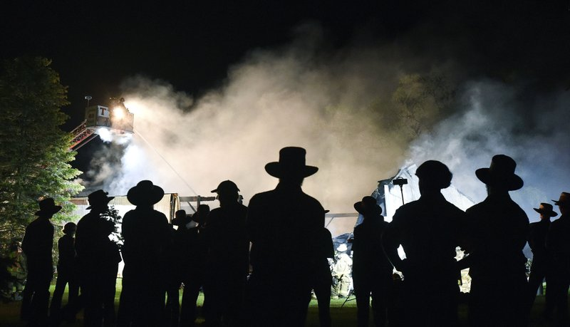 In this Wednesday, May 29, 2019 photo, Amish farmers stand and watch as firefighters battle a barn fire at Pop's Produce in Strasburg Township, Pa. (Chris Knight/LNP/LancasterOnline via AP)