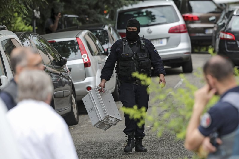 A hooded police officer holds a box during searches at a suspect's home following a blast in Lyon, Monday May 27, 2019 in Oullins, central France. French police have arrested four suspects following a blast in the city of Lyon that wounded 13 people last week, authorities said Monday. (AP Photo/Laurent Cipriani)