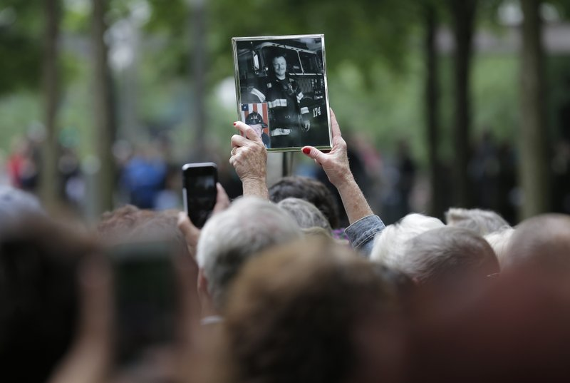 Maureen Fritz holds up a picture of her brother, William Gormley, during a dedication ceremony for a new memorial glade at the World Trade Center in New York, Thursday, May 30, 2019. Gormley died from illness related to his recovery work at ground zero. Former New York City Mayor Michael Bloomberg says the new memorial glade