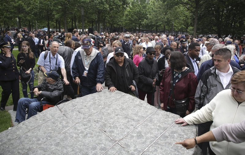 People gather around stones that are part of a new memorial glade at ground zero after a dedication ceremony in New York, Thursday, May 30, 2019. Former New York City Mayor Michael Bloomberg says the new memorial glade at the World Trade Center site