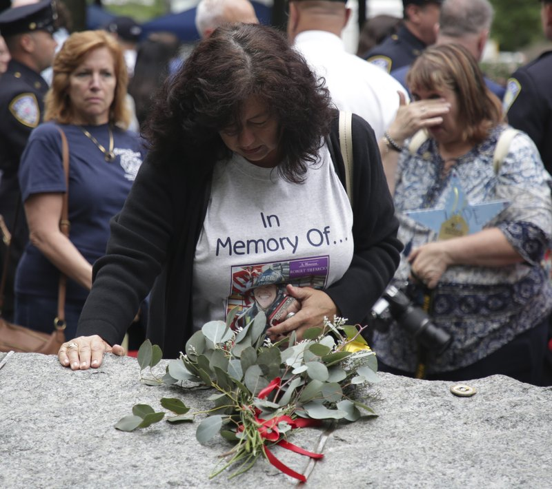 Tina Tilearcio pauses at a stone that is part of a new memorial glade at ground zero after a dedication ceremony in New York, Thursday, May 30, 2019. Her husband, Robert Tilearcio, died in 2017 of illness related to his recovery work at ground zero. Former New York City Mayor Michael Bloomberg says the new memorial glade at the World Trade Center site