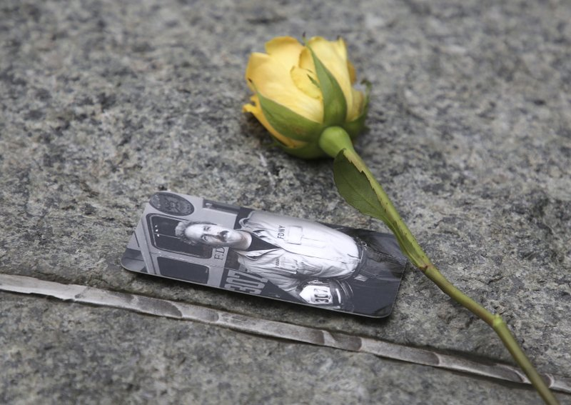 People left flowers and photos on stones that are part of a new memorial glade at ground zero after a dedication ceremony in New York, Thursday, May 30, 2019. Former New York City Mayor Michael Bloomberg says the new memorial glade at the World Trade Center site