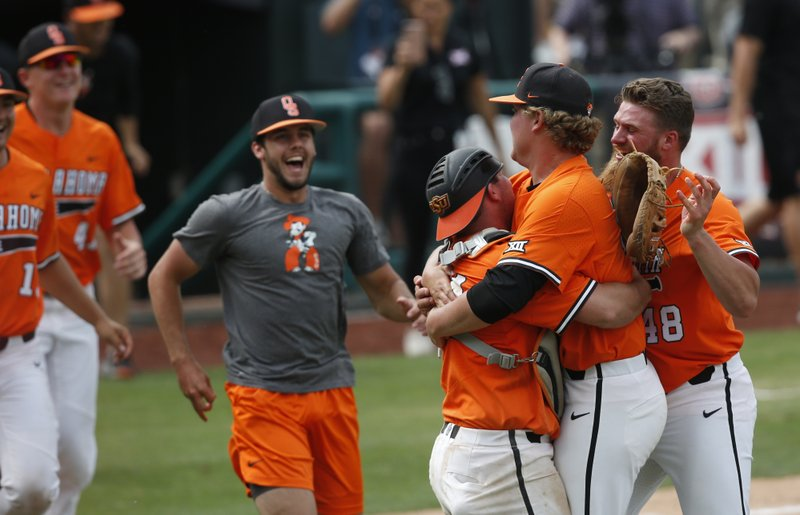Oklahoma State starting pitcher Brett Standlee, right, runs out to the mound with other teammates as catcher Colin Simpson and relief pitcher Peyton Battenfield, second from right, celebrate at the end of the championship game of the NCAA college Big 12 baseball tournament against West Virginia Sunday, May 26, 2019, in Oklahoma City. Oklahoma State won 5-2. (AP Photo/Sue Ogrocki)