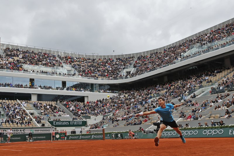 Austria's Dominic Thiem stretches to return a shot against Kazakhstan's Alexander Bublik, rear left, during their second round match of the French Open tennis tournament at the Roland Garros stadium in Paris, Thursday, May 30, 2019. (AP Photo/Pavel Golovkin)