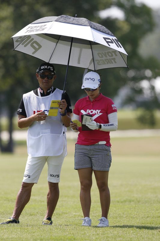 Mamiko Higa of Japan, views her yardage book as her caddie Ei Kawato holds an umbrella during the first round of the U.S. Women's Open golf tournament, Thursday, May 30, 2019, in Charleston, S.C. (AP Photo/Mic Smith)