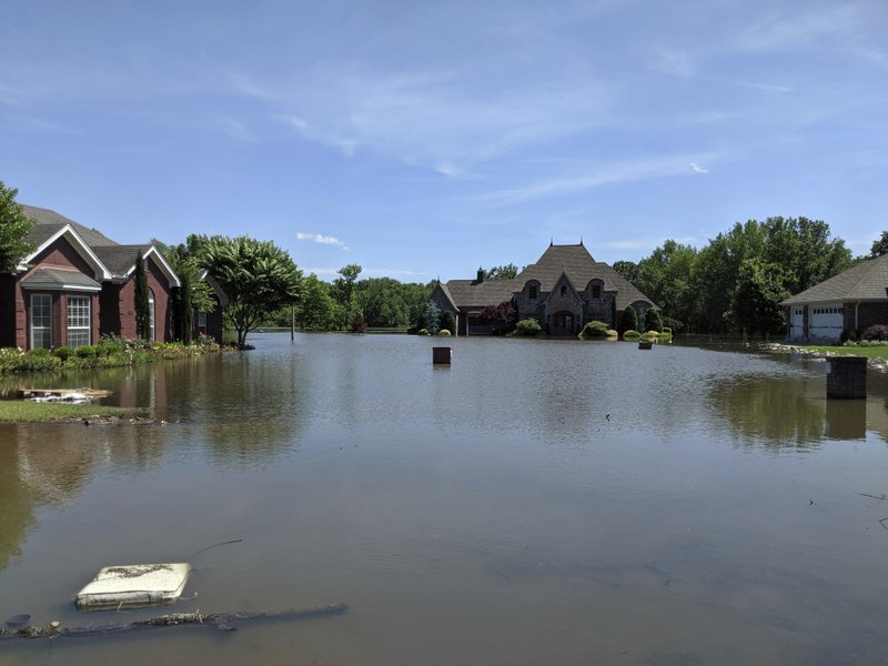 Flood waters surround homes, Thursday, May 30, 2019 in Fort Smith, Ark. The Arkansas River held steady at record levels Thursday, putting enormous pressure on aging levees and offering little relief to areas enduring historic flooding. (Hannah Grabenstein/AP)