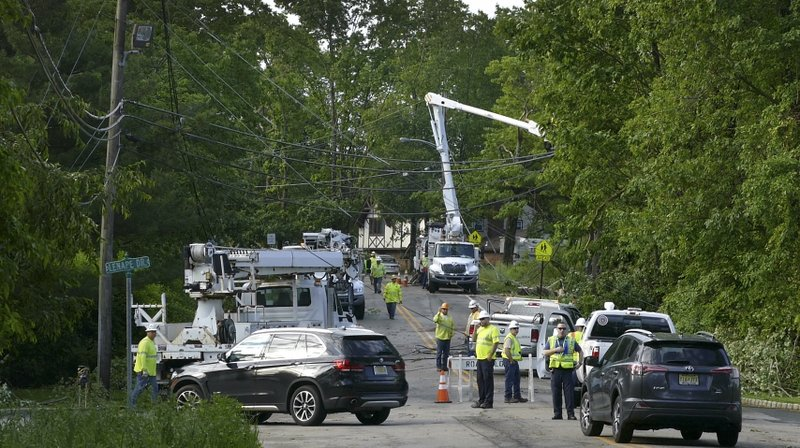 Technicians work  on downed power lines near the entrance of Lenape Valley Regional High School in Stanhope, N.J. on Wednesday, May 29, 2019.  Lenape Valley Regional High School is closed Wednesday after a storm damaged its facade and ripped up a dugout from its baseball field Tuesday evening. The town also experienced fallen tree branches and downed power lines.  (Michael Mancuso/NJ Advance Media via AP)