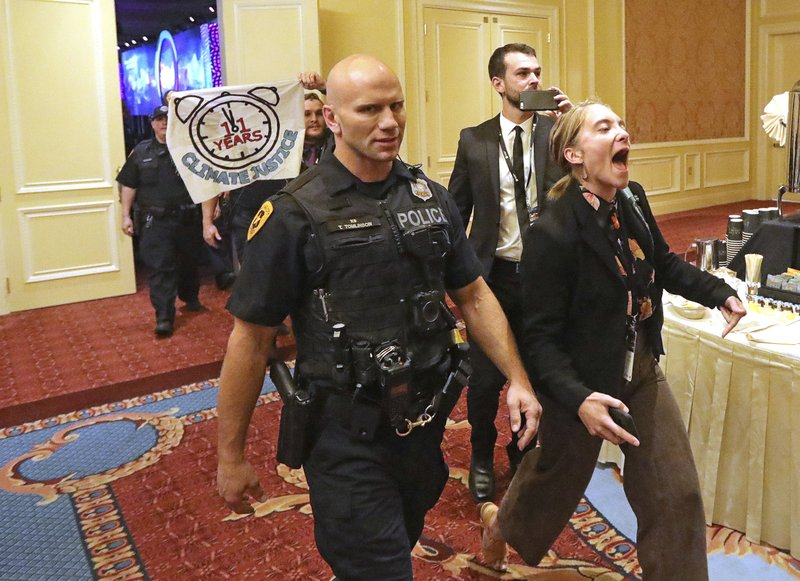 About 25 protesters are escorted by police after interrupting a energy summit conference where U.S. Energy Secretary Rick Perry spoke Thursday, May 30, 2019, in Salt Lake City. Perry says the Trump administration is committed to making fossil fuels cleaner rather than imposing