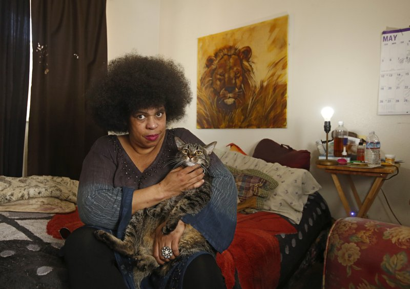 In this May 23, 2019, photo, Kallithea Miller poses for the photo in her bedroom with her cat, Mojo, in Stockton, Calif. Miller suffers from sleep apnea and uses an electric CPAP machine to keep her breathing while she sleeps at night, says she depends on her cat to wake her if the power goes out and her CPAP stops working. Pacific, Gas & Electric Co. initially planned to de-energize local powers lines in vulnerable rural areas during high winds, but has expanded its precautionary power outages to urban areas, which could endanger some who depend on electricity for their life support like Miller. (AP Photo/Rich Pedroncelli)
