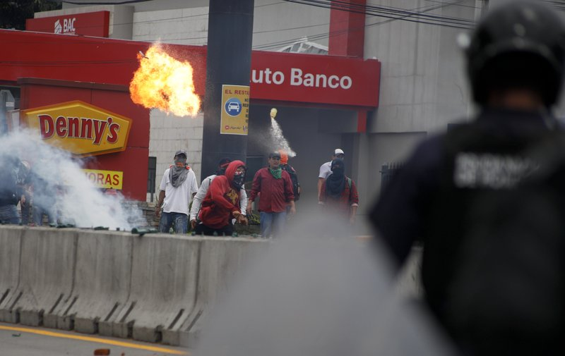 A man throws a molotov cocktail at the police during a protest against the government of Honduras' President Juan Orlando Hernandez in Tegucigalpa, Honduras, Thursday, May 30, 2019. Thousands of doctors and teachers have been marching through the streets of Honduras' capital for the last three weeks, against presidential decrees they say would lead to massive public sector layoffs. (AP Photo/Elmer Martinez)