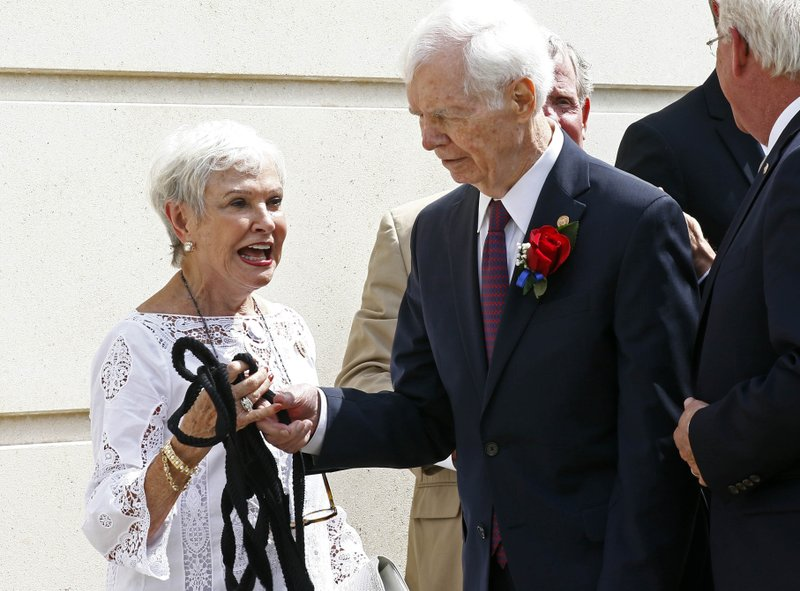 FILE - In this Aug. 9, 2018 file photo, former U.S. Sen. Thad Cochran, right, and his wife Kay Webber, react to a ripped rope attached to the veil over Cochran's name during the unveiling prior to the naming ceremony of the Thad Cochran United States Courthouse in downtown Jackson, Miss. Seven-term Republican Sen. Thad Cochran, who used seniority to steer billions of dollars to his home state of Mississippi, died Thursday, May 30, 2019. He was 81.  (AP Photo/Rogelio V. Solis, File)