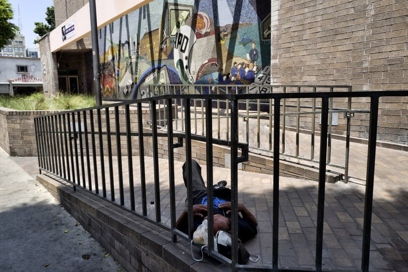 A homeless man sleeps on the front walkway of LAPD Central Community Police Station in downtown Los Angeles on Thursday, May 30, 2019. The union that represents the LAPD is demanding a cleanup of homeless encampments in the city after one detective who works downtown was diagnosed with typhoid fever and two others are showing similar symptoms. (AP Photo/Richard Vogel)