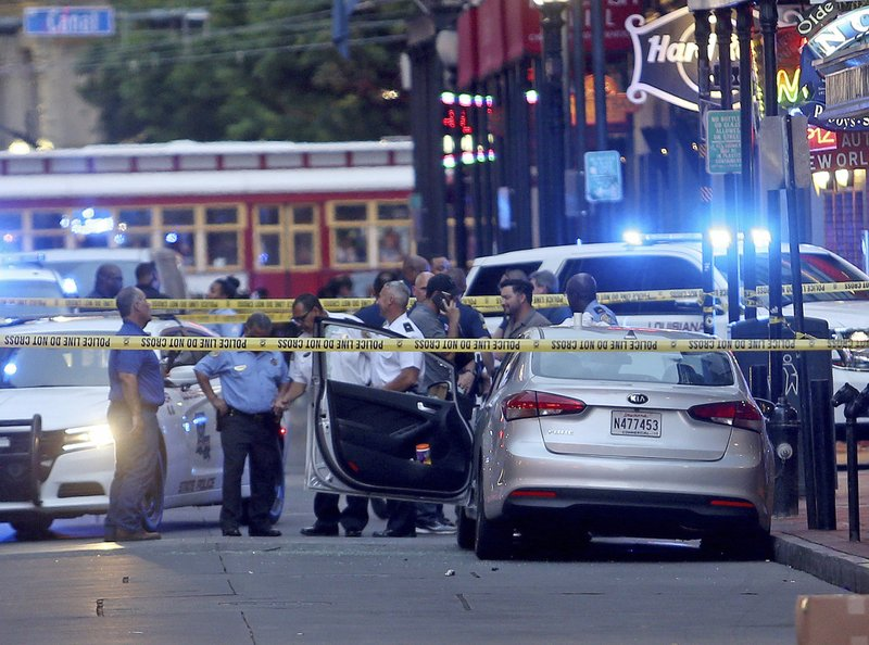 Investigators look at a Kia Forte with a shattered driver's window after a Louisiana state trooper shot the driver of the car on tourist-filled Bourbon Street in the French Quarter of New Orleans, on Thursday, May 30, 2019. (Michael DeMocker/NOLA.com/The Times-Picayune via AP)