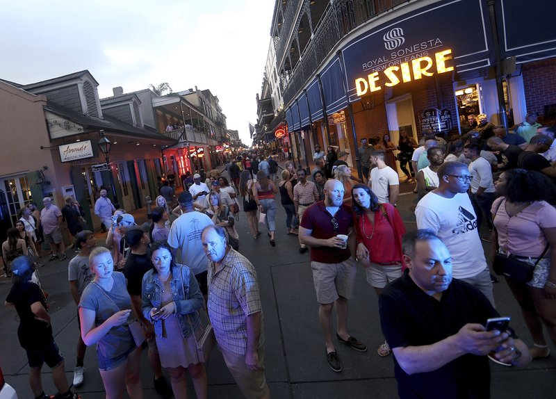 People gather to watch on Bourbon Street at Bienville Street after a Louisiana state trooper shot a driver of a car on tourist-filled Bourbon Street in the French Quarter of New Orleans, on Thursday, May 30, 2019. (Michael DeMocker/NOLA.com/The Times-Picayune via AP)