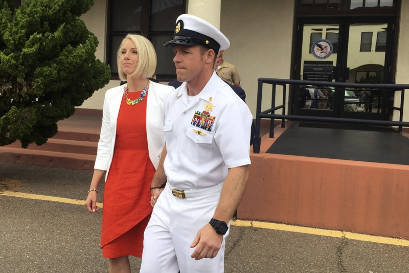 Navy Special Operations Chief Edward Gallagher leaves a military courtroom on Naval Base San Diego with his wife, Andrea Gallagher, Thursday, May 30, 2019, in San Diego. The decorated Navy SEAL facing a murder trial in the death of an Islamic State prisoner was freed Thursday from custody after a military judge cited interference by prosecutors. (AP Photo/ Julie Watson)