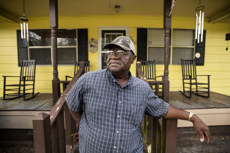 In this May 13, 2019, photo, lifelong Nichols, S.C., resident Thomas Lee, poses for a portrait in front of his freshly painted home. When the first drops of rain from Florence fell last September, Lee considered leaving. But exactly 238 days later, he put the last coat of bright yellow paint on his walls, covering the 2018 high-water mark, several inches above the 2016 line from Hurricane Matthew. (AP Photo/Sean Rayford)
