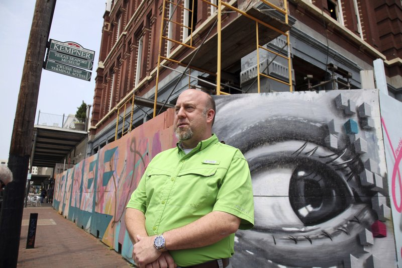 "In this May 9, 2019, photo, business owner Keith Bassett discusses his effort to renovate a building in the Strand, the Galveston, Texas, historic downtown district. The restoration of the historic building is part of an ongoing rebirth of downtown Galveston following the devastation the city suffered when Hurricane Ike made landfall in 2008. ""The city is definitely doing really well,"" said Bassett, who rebuilt and consolidated his two stores that were flooded. (AP Photo/John L. Mone)"