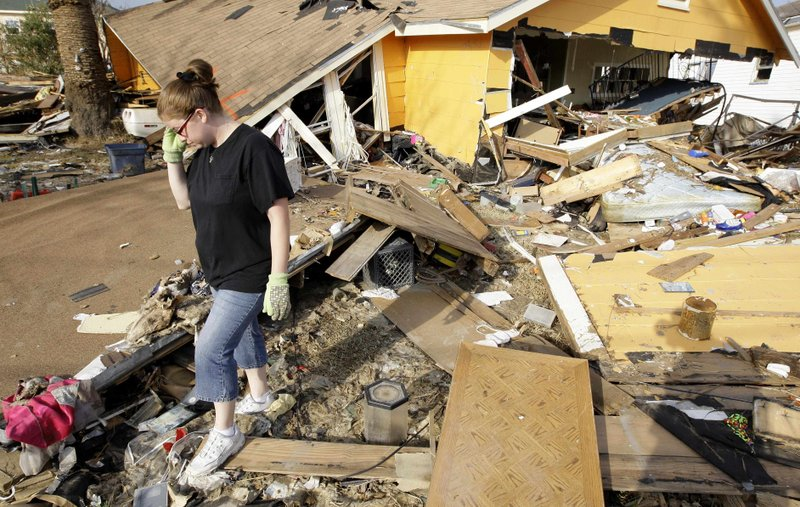 FILE - In this Sept. 24, 2008, file photo, Gina Hadley walks through what's left of her home in the aftermath of Hurricane Ike in Galveston, Texas. It's been nearly 11 years since Hurricane Ike devastated homes on the Texas island and wiped away beaches that were the lifeblood of its tourism economy. (AP Photo/David J. Phillip, File)