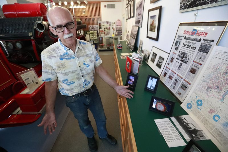 In this, Monday, May 6, 2019, photo, Jeff Blakley shows off some of the photos and newspapers documenting the destruction to the town by Hurricane Andrew on display at the Historic Homestead Town Hall Museum in Homestead, Fla. Blakely remembers watching the exodus while pulling 12-hour shifts as a BellSouth lineman, repairing telephone lines for the ravaged area. (AP Photo/Wilfredo Lee)