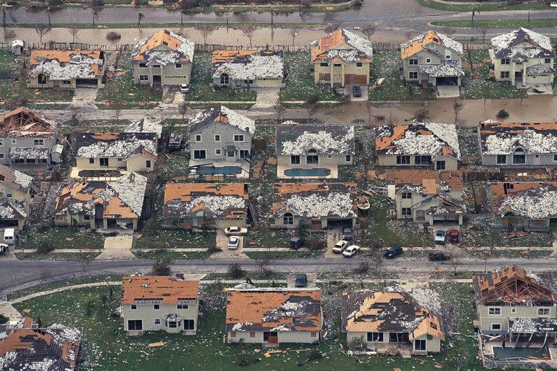 FILE - This Aug. 25, 1992, file photo shows rows of damaged houses between Homestead and Florida City, Fla. In 1992, Homestead was a sleepy agricultural town bordered by the Everglades and large farms planted with winter tomatoes and other crops. Now Homestead is full of sprawling gated developments where many residents commute north to Miami with no memory of the monster storm. (AP Photo/Mark Foley, File)
