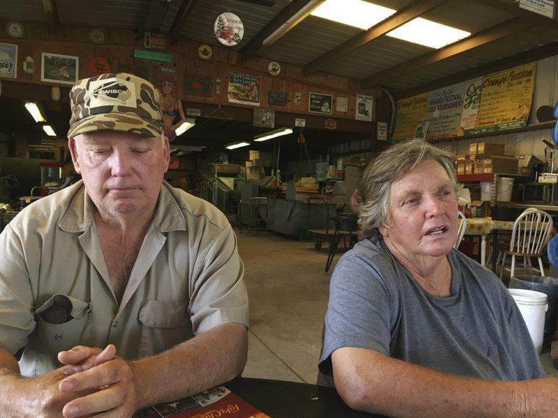 In this May 9, 2019, photo, siblings John and Patty Vogt sit at a table at their family-owned produce business in Plaquemines Parish, La. In its aftermath of Hurricane Katrina, Patty managed to salvage and rebuild the 60-foot (18-meter) contraption that washes, rinses and dries their harvest. But their citrus business never fully recovered. (AP Photo/Kevin McGill)