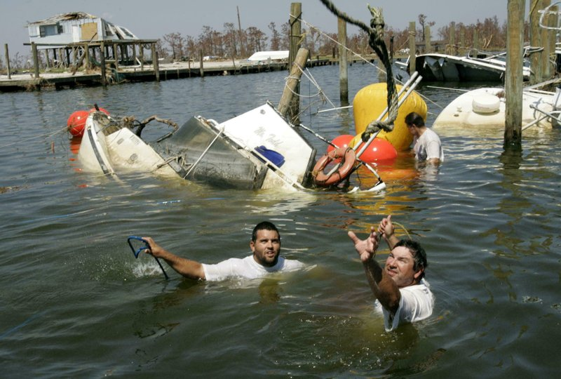 FILE - In this Sept. 11, 2005, file photo, Danny Hebert, right, reaches for a rope at the Venice Marina in the aftermath of Hurricane Katrina in Venice, La., which is part of Plaquemines Parish. Also pictured, Lee Schouest, left, and Clint Boquet, back, try to right the Mr. Todd charter fishing boat. (Erich Schlegel/The Dallas Morning News via AP, File)