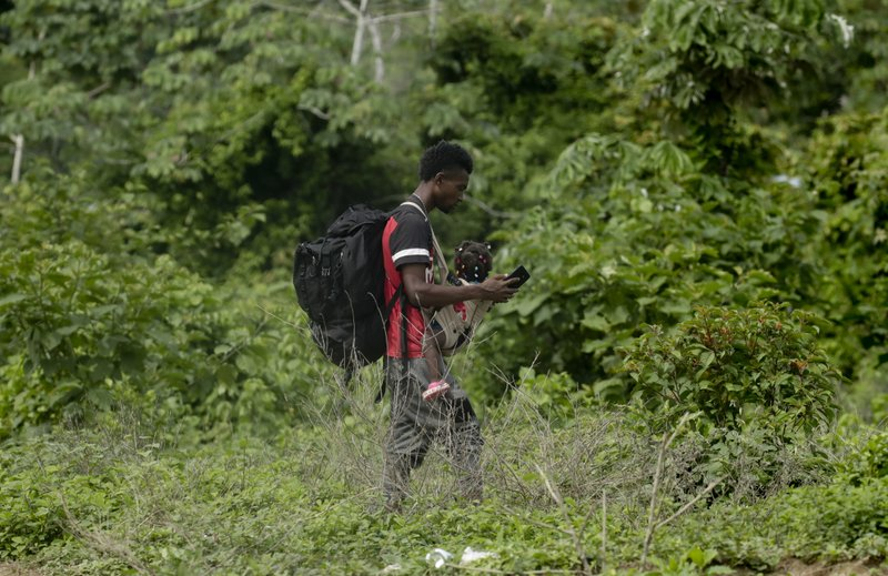 In this May 25, 2019 photo, a migrant carrying a girl walks near the Tuquesa river, in Bajo Chiquito, Darien province, Panama. Panamanian President Juan Carlos Varela said last week that at least 4,000 migrants were in Bajo Chiquito, Penitas and in western Panama near Costa Rica, the next stop on the road north to the United States. (AP Photo/Arnulfo Franco)