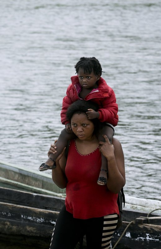 In this May 25, 2019 photo, a migrant woman carries her child on her shoulders after wading across the Tuquesa river in Bajo Chiquito, Darien province, Panama. The woman and her child had walked for many days in the jungle before arriving in Bajo Chiquito. (AP Photo/Arnulfo Franco)