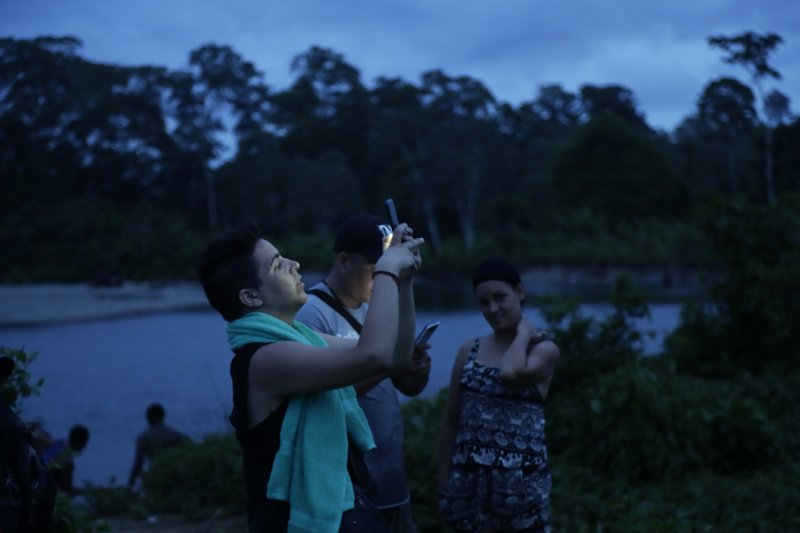 In this May 24, 2019 photo, Cuban migrants look for cellphone signal in Bajo Chiquito, Darien province, Panama. The group wanted to contact their relatives and report on their progress. (AP Photo/Arnulfo Franco)