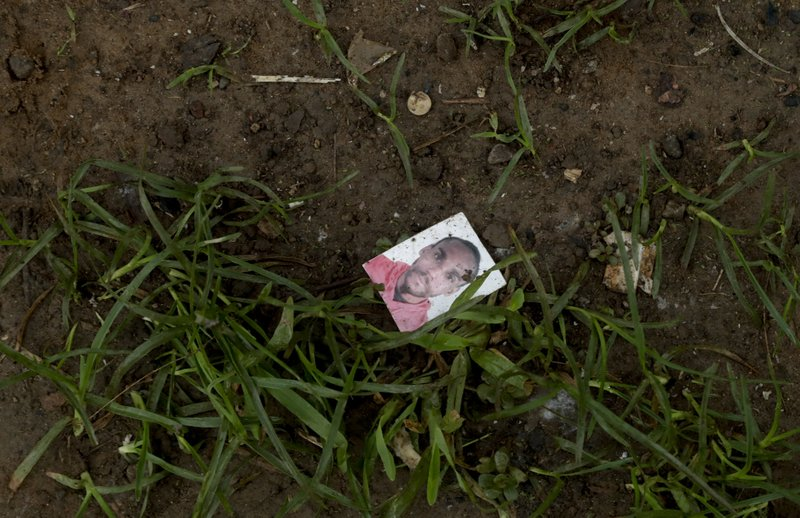 In this May 25, 2019 photo, the mugshot of an unknown migrant lays on the ground in Bajo Chiquito, Darien province, Panama. As migrants surge on the country's borders, Panamanian President Juan Carlos Varela acknowledged the difficulty of dealing with problem, which has left authorities scrambling to impose order. (AP Photo/Arnulfo Franco)