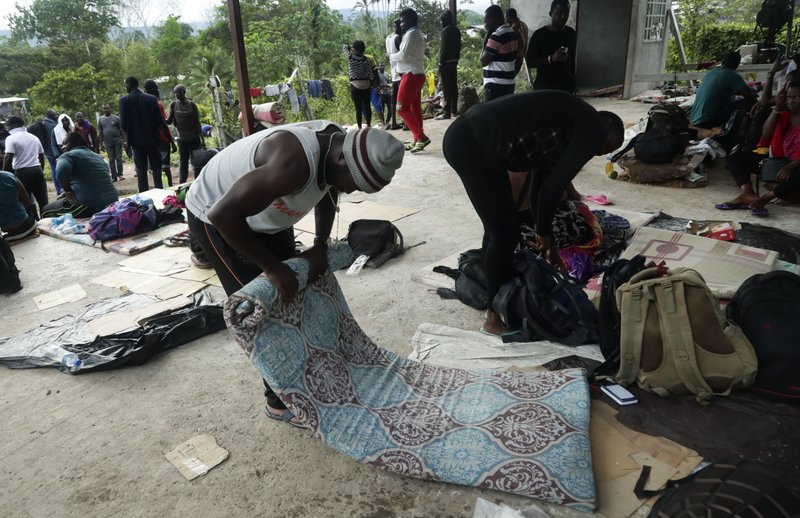 In this May 25, 2019 photo, a migrant from Cameroon rolls up his mattress in Bajo Chiquito, Darien province, Panama. The migrants wait about 10 days in Bajo Chiquito for a two hour boat trip to their next stop on their way north, the village of Peñitas. (AP Photo/Arnulfo Franco)