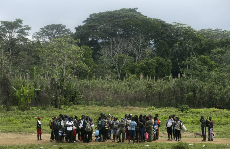 In this May 25, 2019 photo, migrants wait for their turn to catch the next boat that will take them to their next stop on their way north, the village of Peñitas, in Bajo Chiquito, Darien province, Panama. The migrants will navigate the Tuquesa river in boat outfitted with and outboard engine. (AP Photo/Arnulfo Franco)