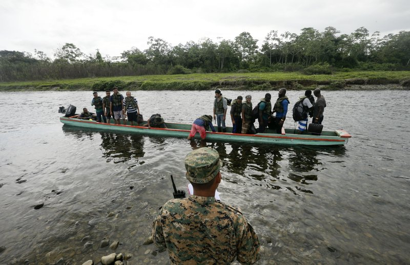 In this May 25, 2019 photo, a police officer count migrants in a boat that will navigate the Tuquesa river on their way to Peñitas, in Bajo Chiquito, Darien province, Panama. According to border police, at least a dozen migrants, likely more, have been killed recently by fast-rising rivers elsewhere in Darien. (AP Photo/Arnulfo Franco)