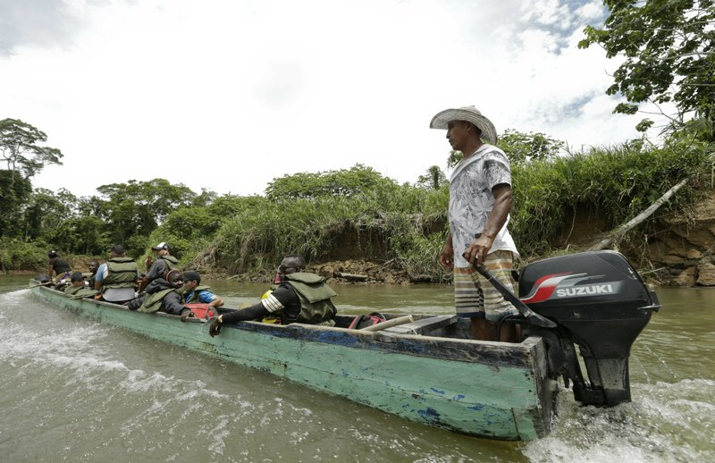 In this May 25, 2019 photo, migrants travel on a dangerously overloaded boat, on the Tuquesa river on their way to Peñitas, from Bajo Chiquito, Darien province, Panama. Boat drivers frequently lift their outboard motors to keep them from colliding with the shallow, rock-filled riverbed, steered toward the brush-lined shore in search of deeper waters and veered to dodge enormous tree trunks ripped out at the roots by previous flash floods. (AP Photo/Arnulfo Franco)