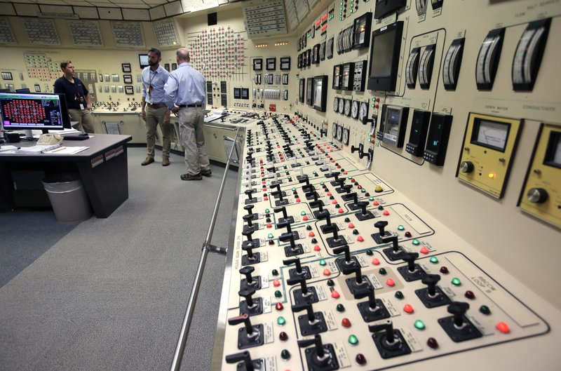 Senior Reactor Operator Christina Renaud, left, speaks with Training Supervisor Paul Gresh, center, and Control Room Supervisor Bob Sheridan, right, in the Control Room Simulator moments before a simulated reactor shutdown, Tuesday, May 28, 2019, at a training facility several miles from the Pilgrim Nuclear Power Station, in Plymouth, Mass. The simulated shutdown was performed in front of members of the media Tuesday ahead of the planned actual shutdown of the aging reactor on Friday, May 31. (AP Photo/Steven Senne)