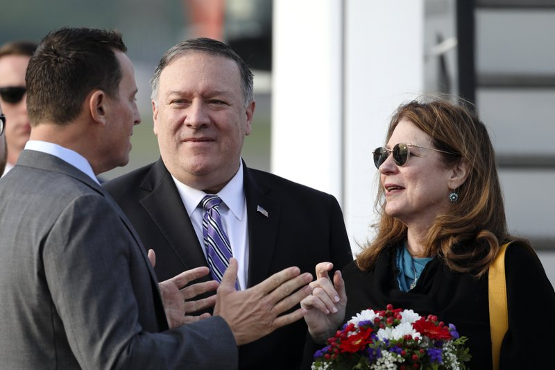 U.S. Secretary of State Mike Pompeo, center, and his wife Suzan are welcomed by U.S. Ambassador to Germany Richard Grenell, left, upon arrival at Tegel airport in Berlin, Germany, Friday, May 31, 2019. Pompeo is in Berlin for a one day visit and will meet Chancellor Angela Merkel and his counterpart Heiko Maas. (AP Photo/Markus Schreiber)
