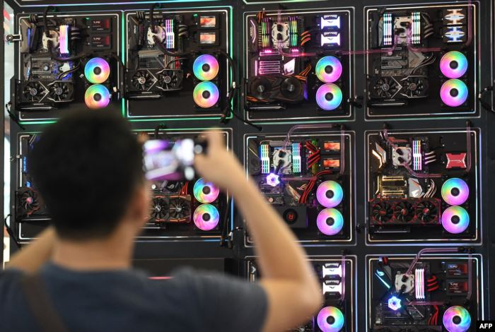 FILE - A visitor takes a picture of LED-enhanced computer motherboards during