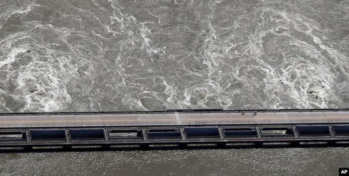 Two cyclists ride along the Old River Control Structure, as swelling waters f