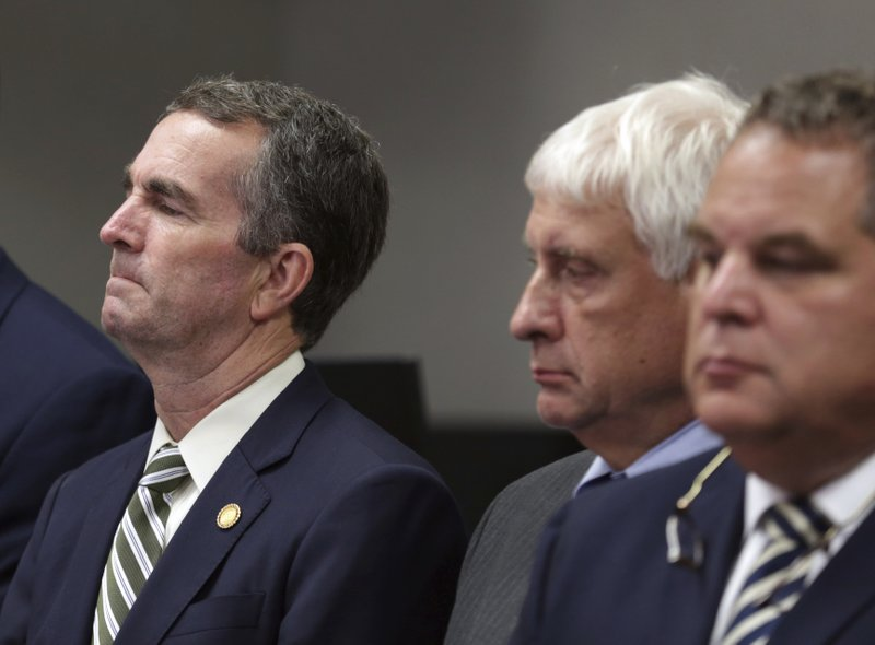 Virginia Gov/ Ralph Northam, left, listens during a news conference in Virginia Beach, Va. Friday, May 31, 2019. A longtime city employee opened fire in a municipal building in Virginia Beach on Friday, killing several people on three floors and sending terrified co-workers scrambling for cover before police shot and killed him following a