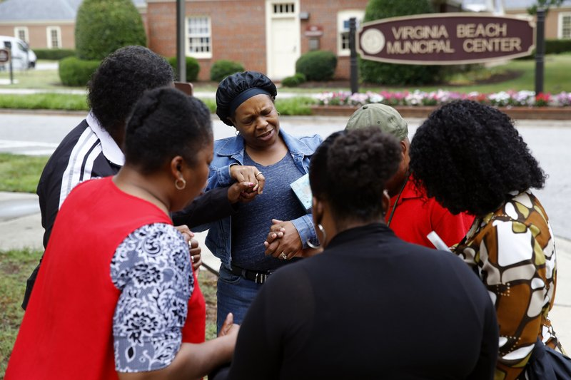 Members of Mount Olive Baptist Church pray near a municipal building that was the scene of a shooting, Saturday, June 1, 2019, in Virginia Beach, Va. A longtime city employee opened fire at the building Friday before police shot and killed him, authorities said. (AP Photo/Patrick Semansky)