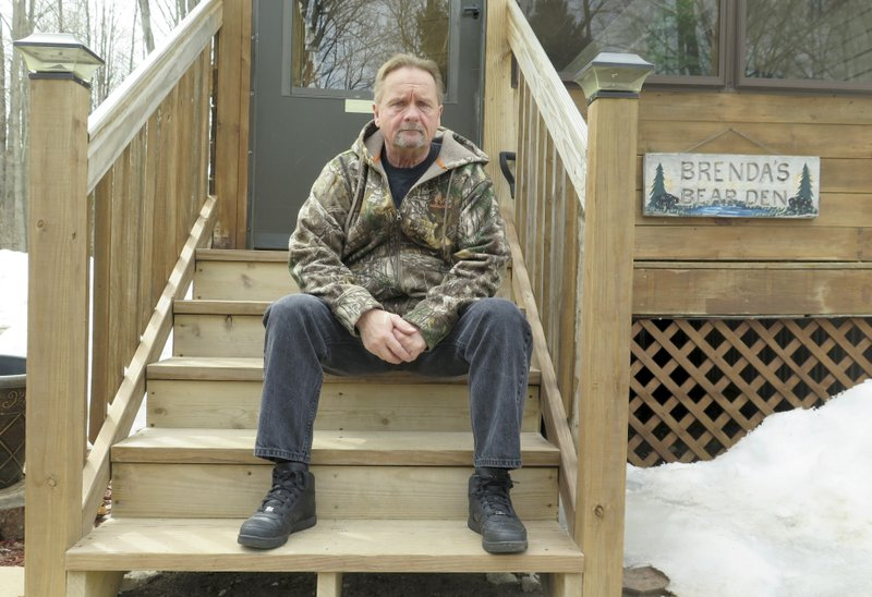 In this April 10, 2019 photo, Wayne Sankey sits on the front steps of his Lakewood, Wis. home where he is the neighbor of Raymand Vannieuwenhoven, who authorities say is the suspect in a cold-blooded 43-year-old cold case murder. The news of Vannieuwenhoven's arrest hit Sankey, 68, like a thunderbolt.   Prosecutors said they used DNA and genetic genealogy to connect Vannieuwenhoven to the 1976 killings of a young couple, David Schuldes and Ellen Matheys. (AP Photo/Ivan Moreno)