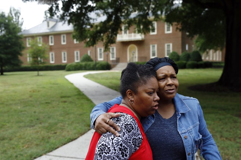 Shelia Cook, left, and Renee Russell, members of Mount Olive Baptist Church, embrace after praying near a municipal building that was the scene of a shooting, Saturday, June 1, 2019, in Virginia Beach, Va. A longtime city employee opened fire at the building Friday before police shot and killed him, authorities said. (AP Photo/Patrick Semansky)