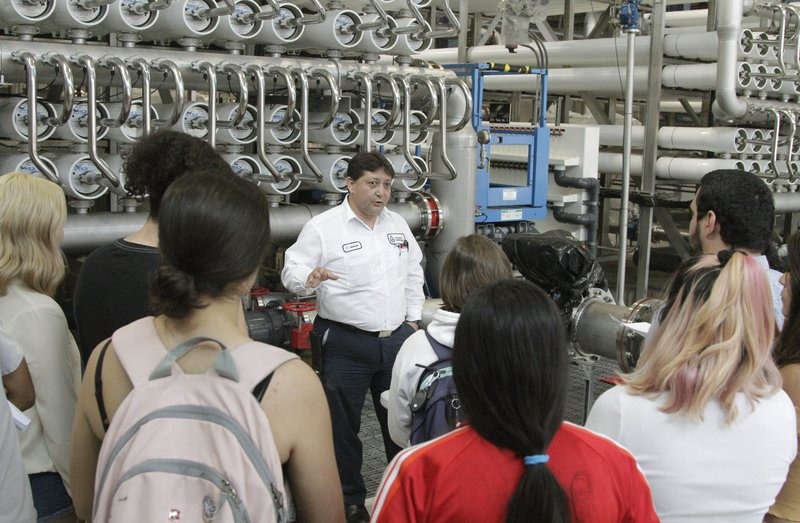 In this May 2, 2019, photo, college students listen as El Paso Water worker Hector Sepulveda explains the desalination process at a plant in El Paso, Texas. The silver pipes push water through tightly packed membranes inside the white pipes, drawing minerals out of the brine. As the planet warms and weather patterns turn more extreme, droughts - as well as floods - in the state generally have worsened. El Paso, which has about 700,000 people living in a desert region that gets only 9 inches (23 centimeters) of rain annually, receives international groups wanting to learn more about innovative facilities like the largest inland desalination plant in the United States. (AP Photo/Cedar Attanasio)