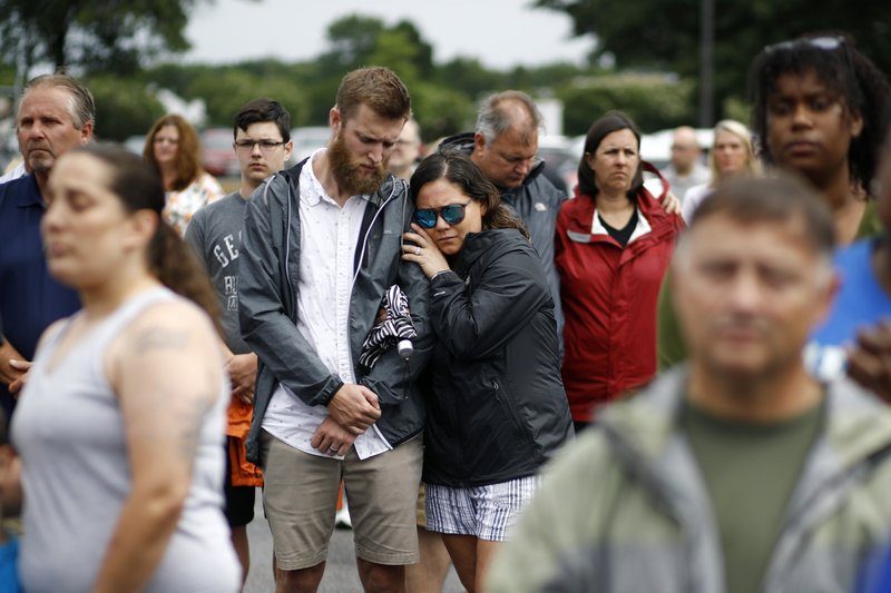 Brittany Myers, right, embraces her husband, Ryan, during a vigil in response to a fatal shooting at a municipal building in Virginia Beach, Va., Saturday, June 1, 2019. A longtime city employee opened fire at the building Friday before police shot and killed him, authorities said. (AP Photo/Patrick Semansky)