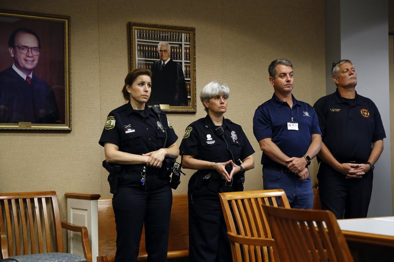 Virginia Beach law enforcement and city officials watch a news conference on a shooting at a municipal building, Saturday, June 1, 2019, in Virginia Beach, Va. Authorities identified the shooting suspect as DeWayne Craddock, a longtime city employee who opened fire at the building Friday before police shot and killed him, authorities said. (AP Photo/Patrick Semansky)