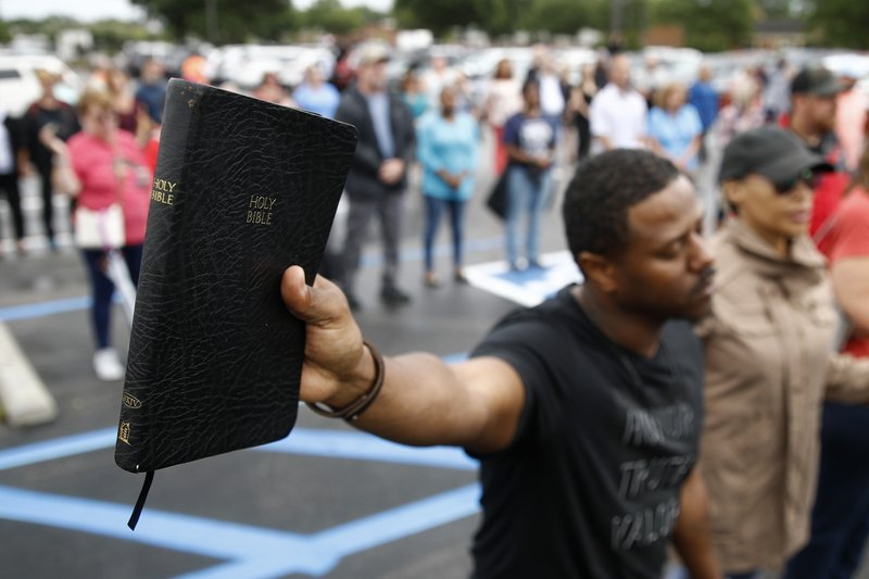 Mike Harris, of Virginia Beach, Va., holds a Bible as he prays during a vigil in response to a shooting at a municipal building in Virginia Beach, Va., Saturday, June 1, 2019. A longtime city employee opened fire at the building Friday before police shot and killed him, authorities said. (AP Photo/Patrick Semansky)