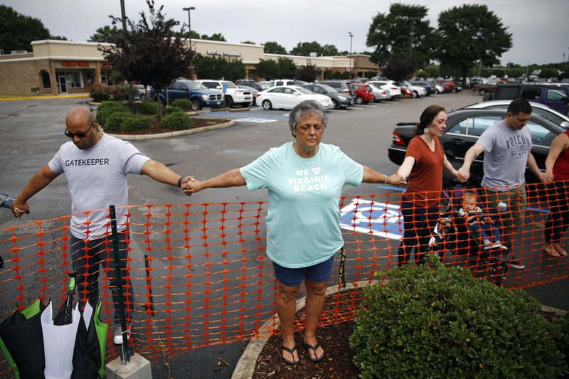 Lisa Dunaway, center, of Virginia Beach, Va., holds hands with gatherers during a vigil in response to a shooting at a municipal building in Virginia Beach, Va., Saturday, June 1, 2019. A longtime city employee opened fire at the building Friday before police shot and killed him, authorities said. (AP Photo/Patrick Semansky)
