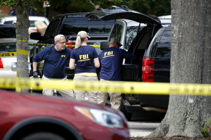 Members of the FBI load equipment into a vehicle as they work in a parking lot outside a municipal building that was the scene of a shooting, Saturday, June 1, 2019, in Virginia Beach, Va. DeWayne Craddock, a longtime city employee, opened fire at the building Friday before police shot and killed him, authorities said. (AP Photo/Patrick Semansky)